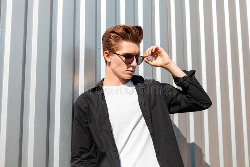 Attractive young man model in a fashionable black shirt in a t-shirt straightens stylish sunglasses. European hipster guy. Posing near a silver metal wall in a stock photo