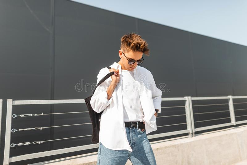 Attractive young man model in summer white fashionable clothes in sunglasses with a cloth black bag stands on a sunny day. Near a gray building in the city royalty free stock photography