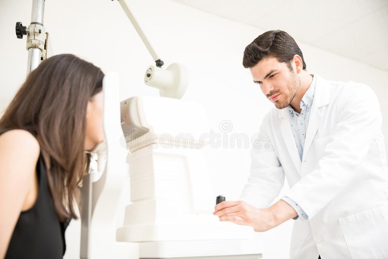 Attractive young man ophthalmologist doing eye examination to woman at clinic stock images