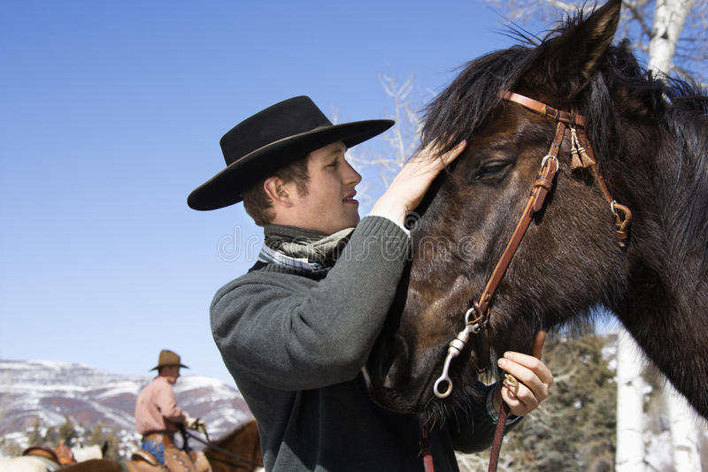 Attractive Young Man Petting Horse royalty free stock photos