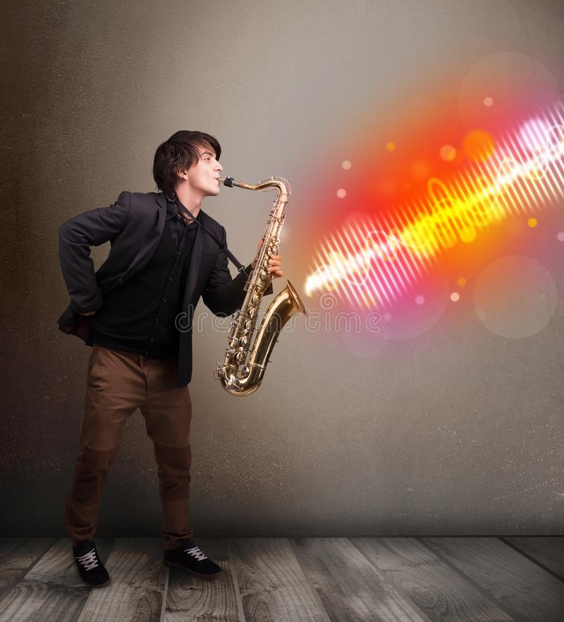 Young man playing on saxophone with colorful sound waves stock image