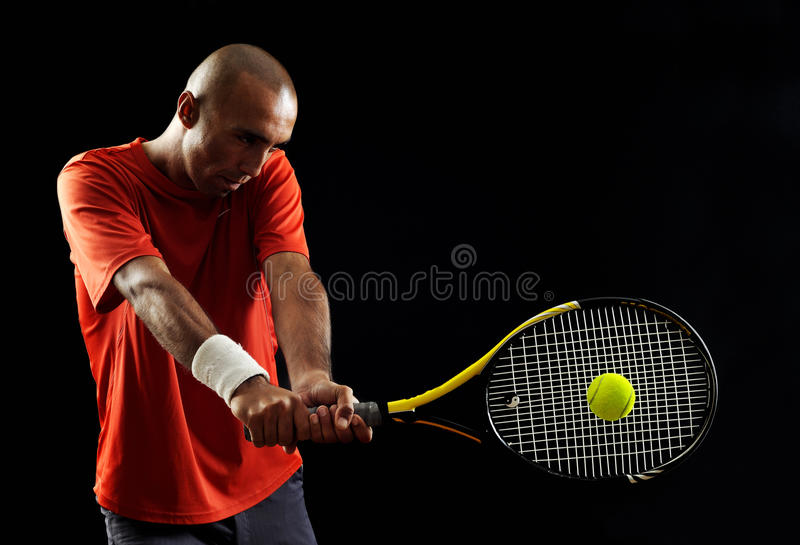 Attractive young man playing tennis portrait. A portrait of a tanned sportive tennis player with a racket against black background royalty free stock photos