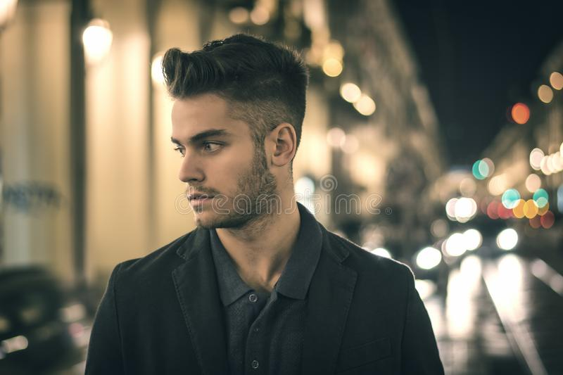 Attractive young man portrait at night with city lights royalty free stock images