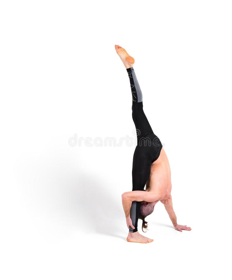 Attractive Young Man practicing advanced yoga on white background. Yoga poses for good health. Sport, meditation and lifestyle co royalty free stock photography