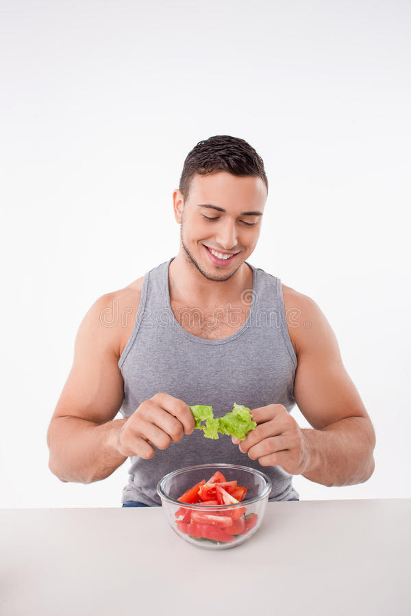 Attractive young man is preparing healthy food. Handsome guy is cooking a salad. He is tearing the leaves of lettuce and throwing it into the plate. The boy is royalty free stock photos