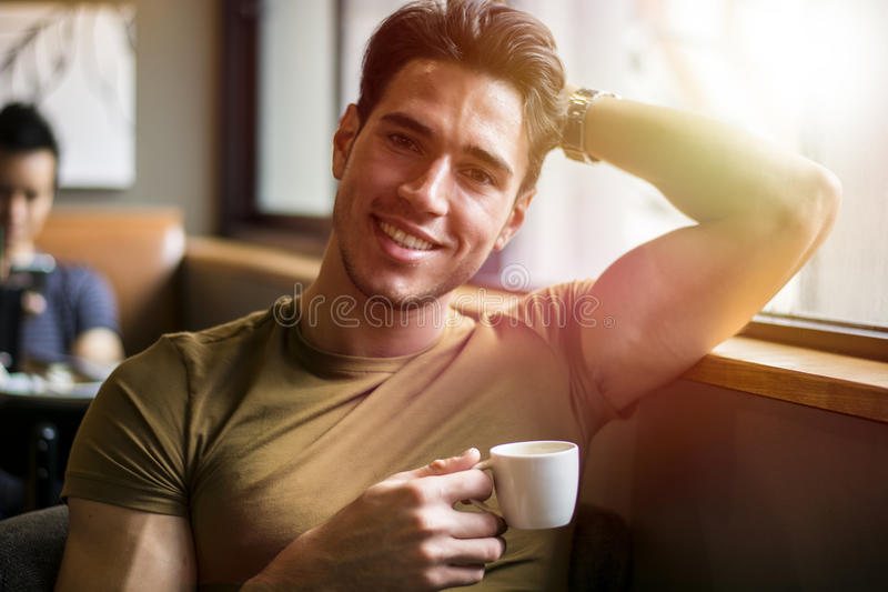Attractive Young Man`s Breakfast, Drinking Coffee. Attractive Young Man Eating Breakfast, Drinking Coffee and Smiling to the Camera stock photo