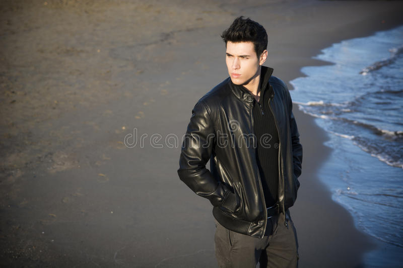 Attractive young man at the seaside on the beach. Handsome fashionable young man at the seaside on the beach with his black leather jacket looking away, large stock photos