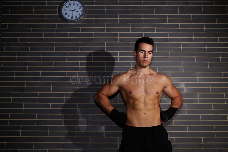 Attractive young man with abdominal looking down royalty free stock image