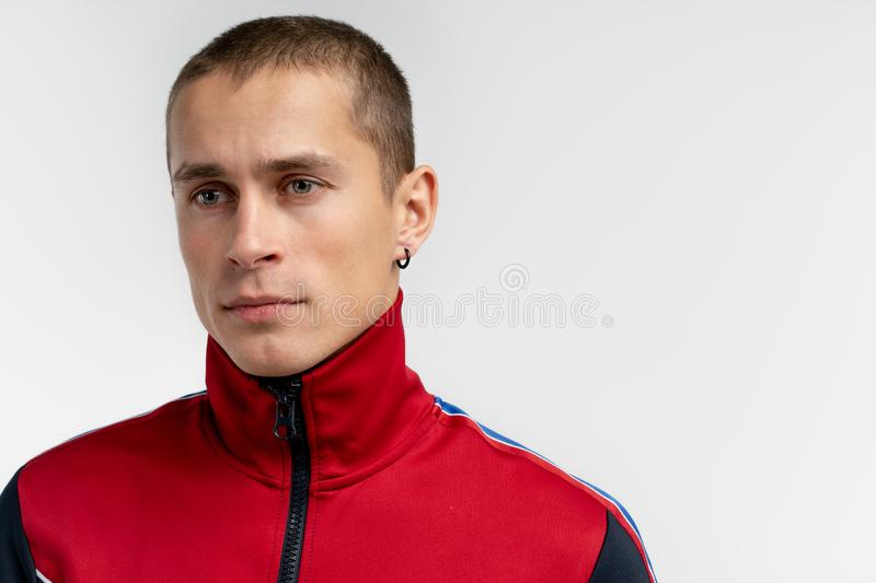 Attractive young man with short haircut and black earrings, wearing casual clothes looking away isolated over white royalty free stock images