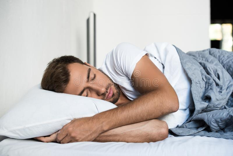 Attractive young man sleeping peacefully. In bed royalty free stock photos
