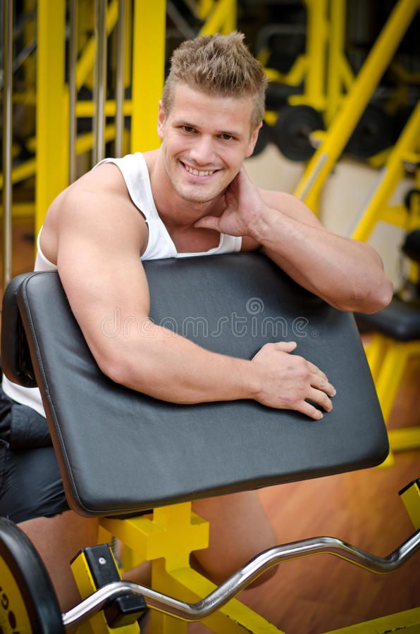 Download Attractive Young Man Smiling On Gym Equipment Stock Photo - Image of trainer, training: 33611904