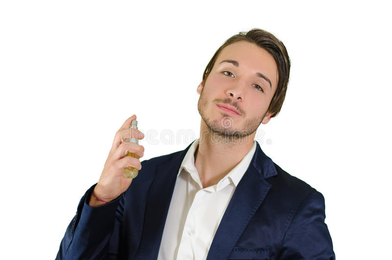 Attractive young man spraying perfume, using fragrance
