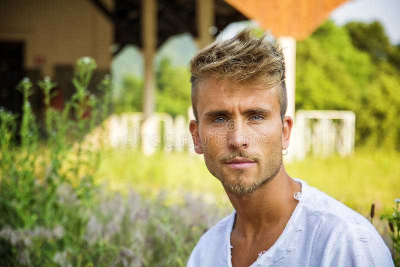 Attractive young man standing by old porch stock image