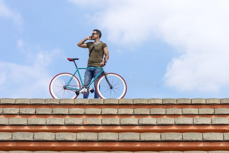 Attractive young man standing outdoors and calling on the phone royalty free stock photos