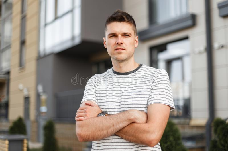 Attractive young man is standing on the street with a phone in his hands. Business handsome guy with a stylish hairstyle. In a fashionable summer T-shirt stock photos