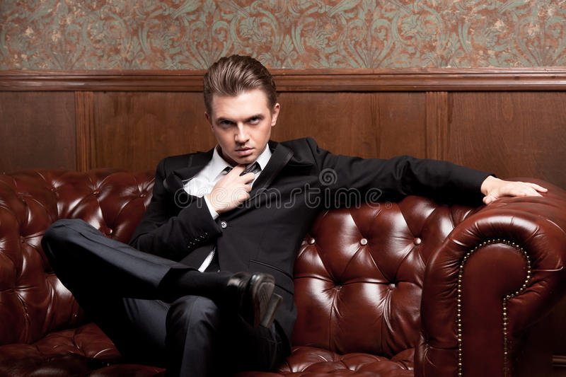 Attractive Young Man In A Suit Sitting On Couch Stock