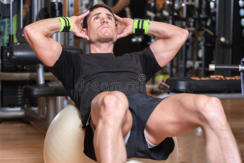 Attractive young man using exercise ball in a gym. Attractive young man exercising abs. stock images