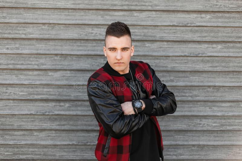 Attractive young man in a vintage plaid jacket with a stylish hairstyle in a t-shirt with a clock poses near a wooden wall royalty free stock images