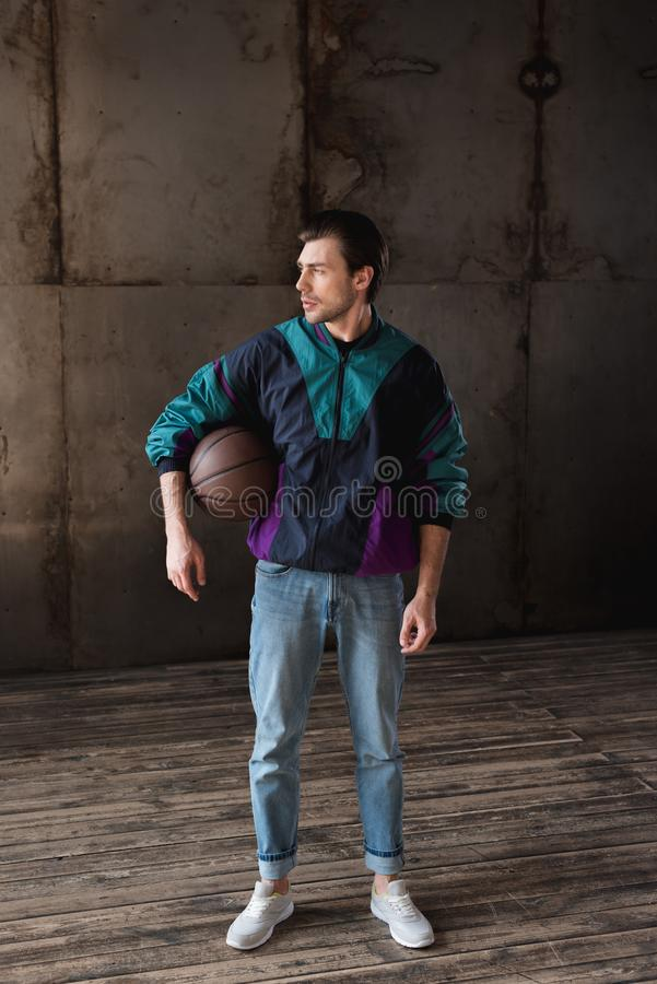 Attractive young man in vintage windcheater with basketball ball. Looking away royalty free stock images