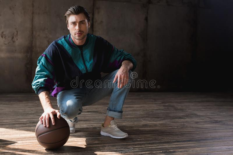 Attractive young man in vintage windcheater with basketball ball sitting squats. On wooden floor stock image