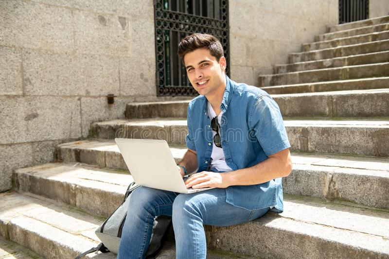 Attractive young modern man working with computer in the city on outside stairs stock photography