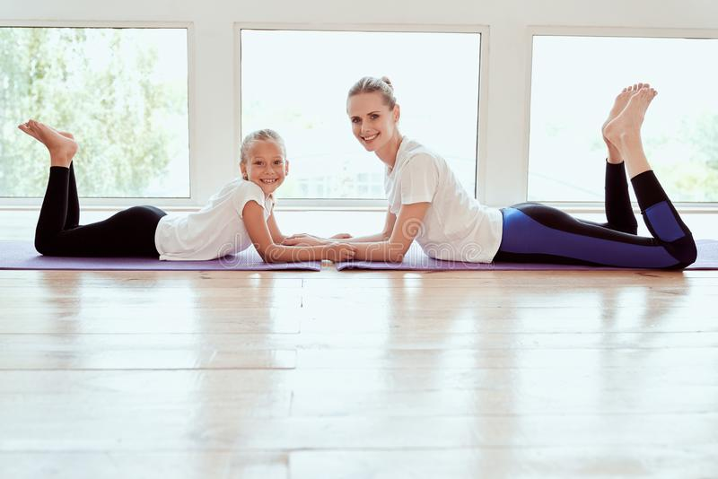 Attractive young mom with her little charming daughter are working out at home. Fitness day. Lying on yoga mat and smiling royalty free stock image