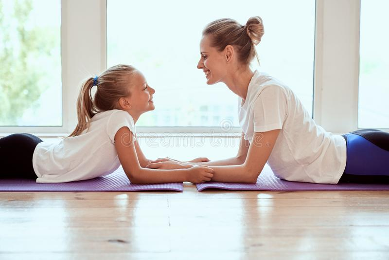 Attractive young mom with her little charming daughter are working out at home. Fitness day. Lying on yoga mat smiling and looking stock photography