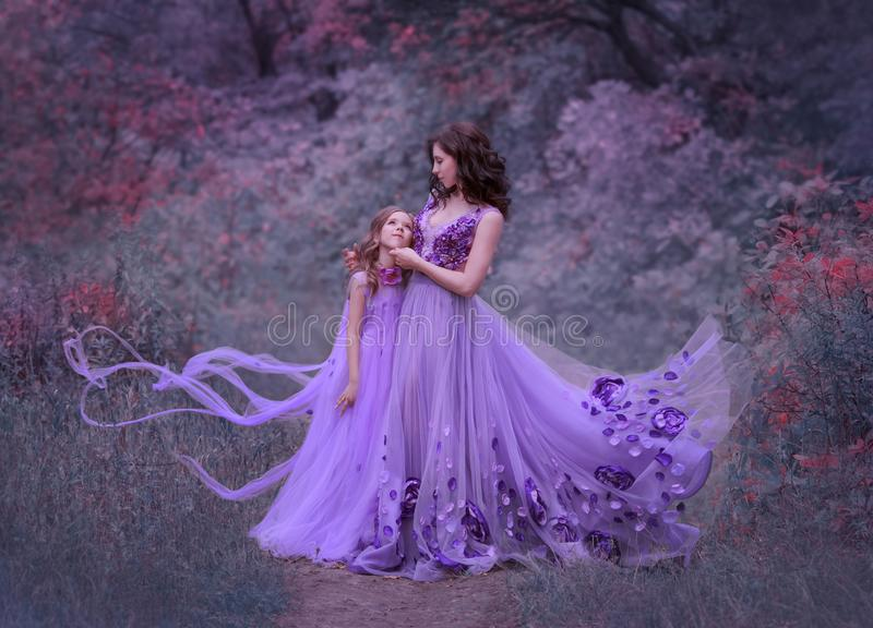 Attractive young mother with dark wavy hair and her little daughter, standing together in the forest in amazing long royalty free stock image