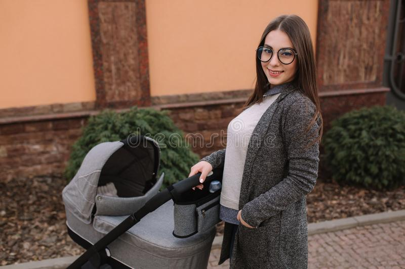 Attractive young mother walking with her little baby. Mom with newborn baby in pram royalty free stock image