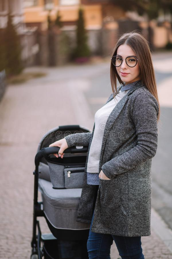 Attractive young mother walking with her little baby. Mom with newborn baby in pram royalty free stock images