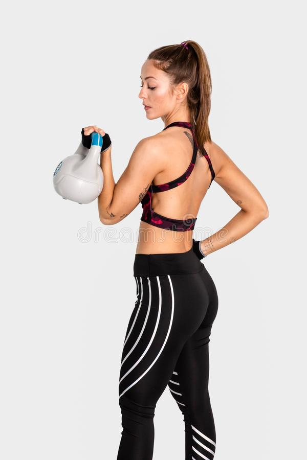 Attractive young with muscular body exercising crossfit. Woman in sportswear doing crossfit workout with kettle bell. Image stock photos