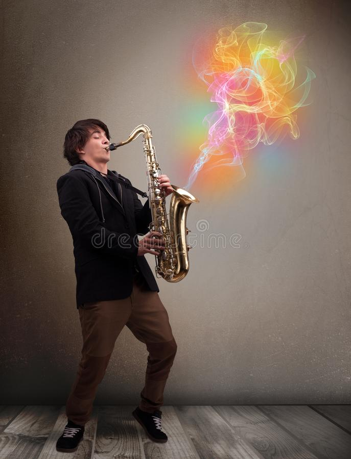 Attractive musician playing on saxophone with colorful abstract. Attractive young musician playing on saxophone with colorful abstract fume comming out stock images