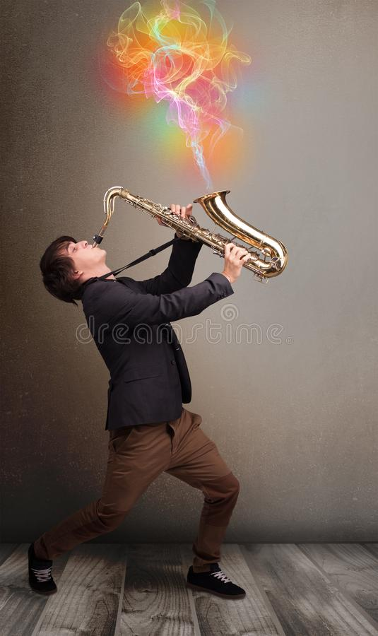 Attractive musician playing on saxophone with colorful abstract stock images