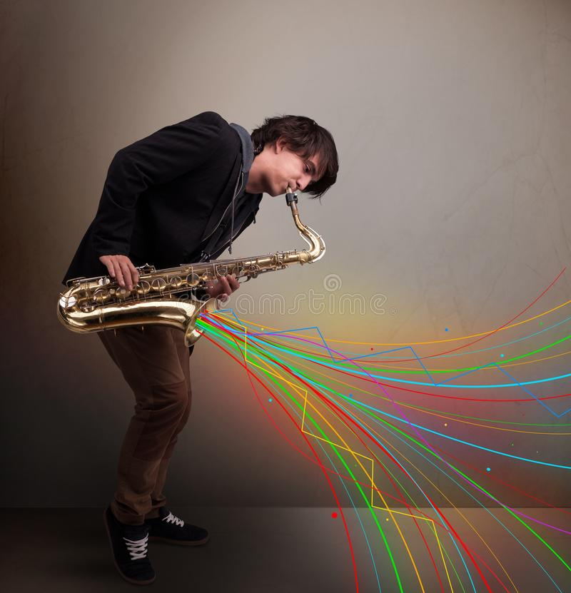 Attractive musician playing on saxophone while colorful abstract royalty free stock images
