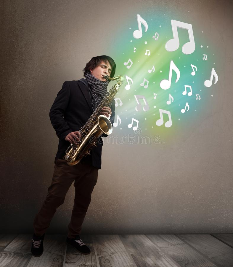 Young musician playing on saxophone while musical notes exploding stock image