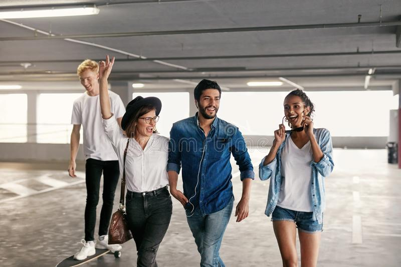Attractive Young People In Casual Fashionable Clothes At Parking. Attractive Young People In Casual Fashionable Clothes At Mall Parking, Stylish Friends Indoors stock photography
