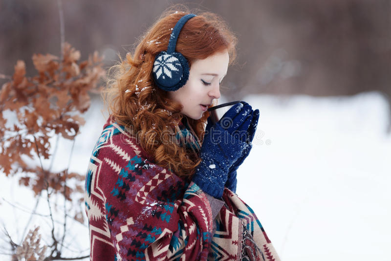 Attractive young red-haired woman drinking a hot drink from a mug. In the winter park. She is wearing a blue headset and gloves and a scarf with ethnic patterns royalty free stock photography