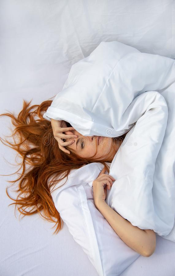 Attractive, young, red-haired woman, hair wild on the sheets, face half under the pillow lying in fresh soft white sheets royalty free stock photo