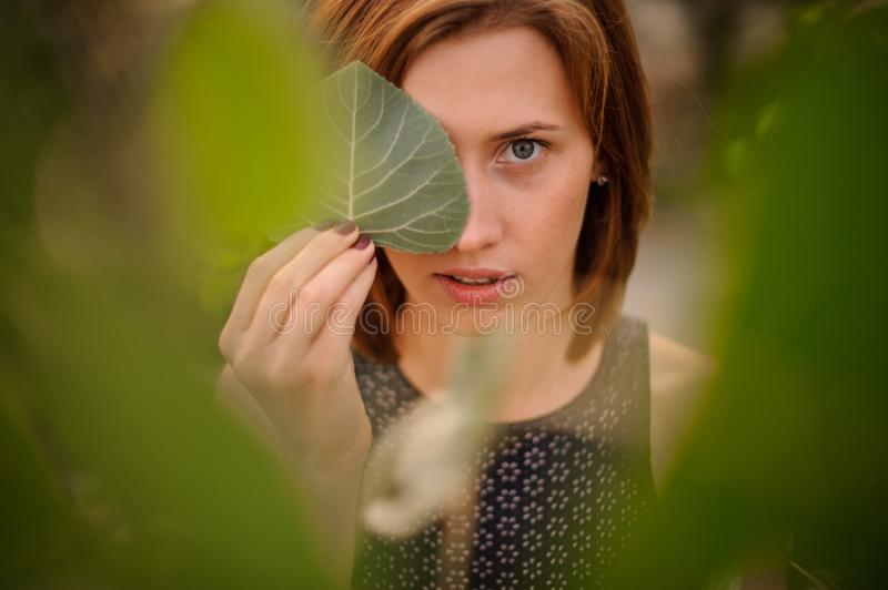 Attractive young redhead girl hiding a half of her face with green leaf royalty free stock image