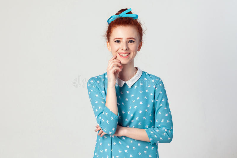The attractive young redhead girl with perfect clean skin looking and smiling at camera with happy and joyful expression touching stock image