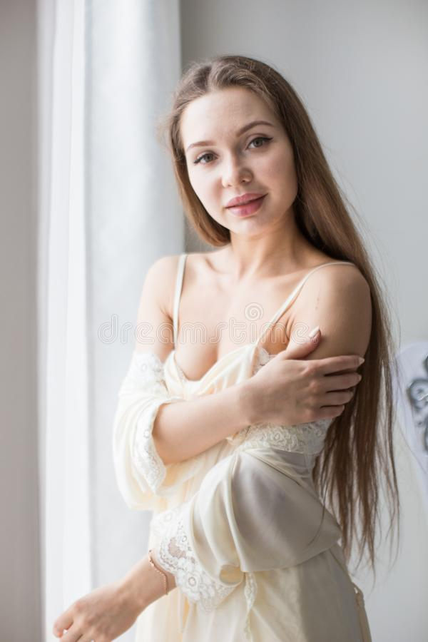 Attractive young seminude girl in night clothes posing sexually by the window.  stock photography