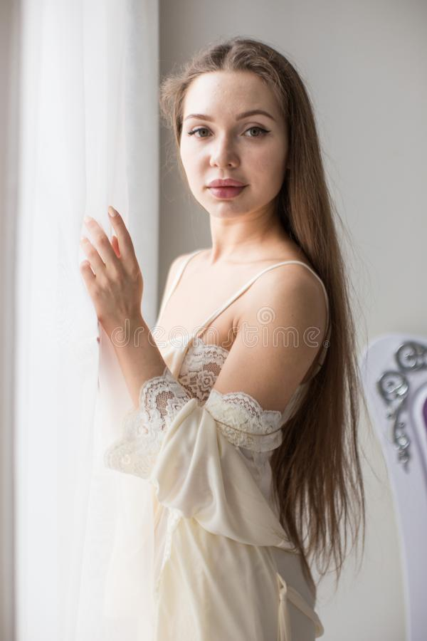 Attractive young seminude girl in night clothes posing sexually by the window.  royalty free stock photo