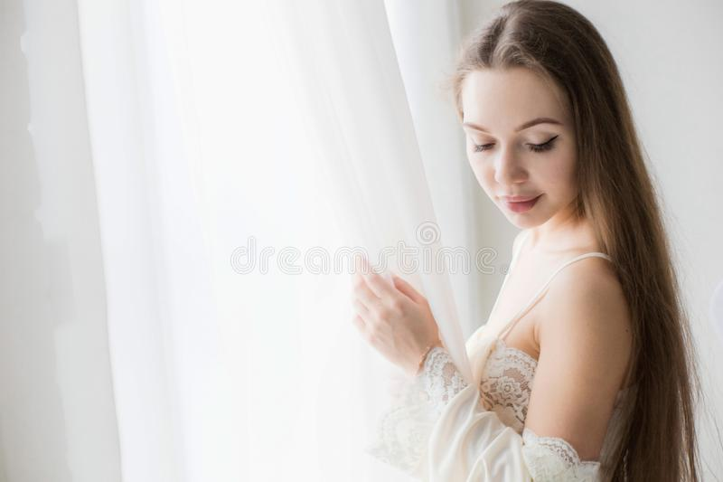 Attractive young seminude girl in night clothes posing sexually by the window.  royalty free stock image