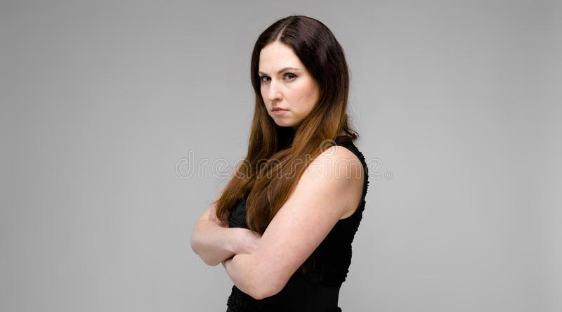 Attractive young serious angry brunette caucasian woman in black dress with crossed arms isolated on gray stock photo