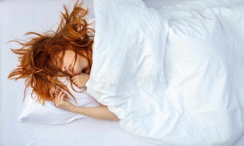 Attractive, young, sexy, red-haired woman, hair wild on the sheets, mouth open, lying in fresh soft white sheets in bedroom royalty free stock photos