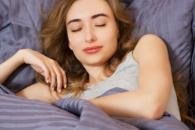 Attractive young smile woman sleeping in bedroom. Healthy lifestyle. Wellness concept royalty free stock image