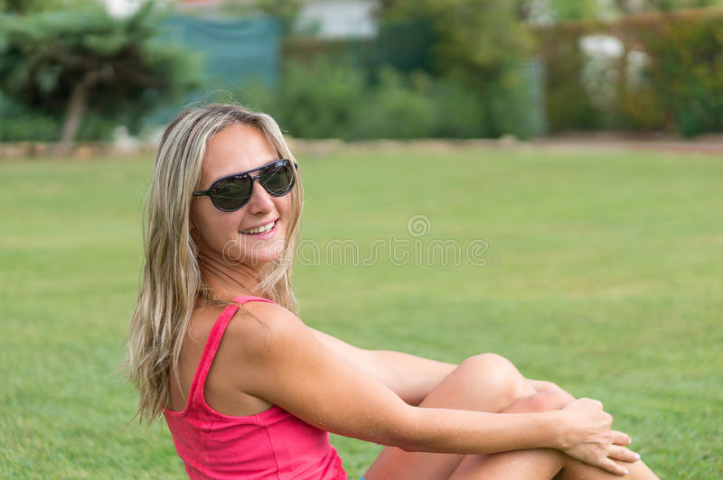 Attractive young smiling beautiful curly blonde hair slim girl fashion portrait in pink T-shirt posing looking away calm look, in royalty free stock images