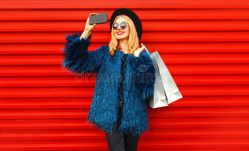 Attractive young smiling woman taking selfie picture by smartphone with shopping bags, stylish female model royalty free stock photos