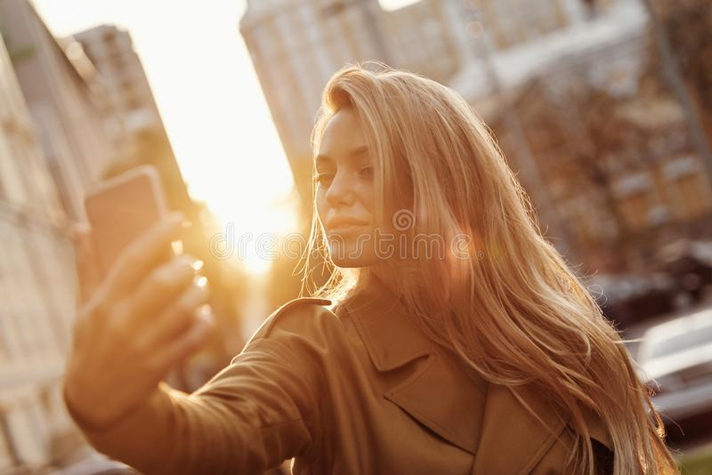 Selfie time!. Attractive young smiling woman taking selfie while spending time in the city stock image
