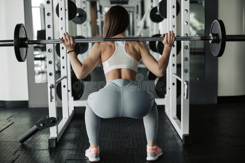 Attractive young sports woman with barbell. Doing squats. Back view royalty free stock photos
